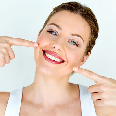 Woman pointing to her smile after cosmetic gum recontouring