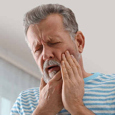 Older man in need of tooth extraction holding jaw