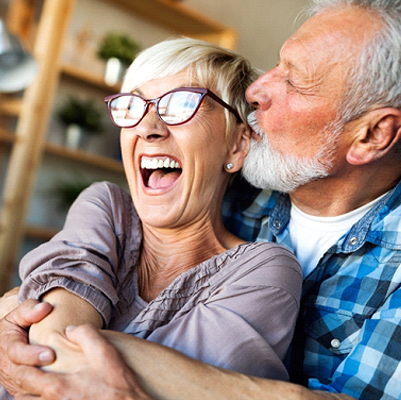 An older couple at home smiling and laughing together after avoiding an appointment with the emergency dentist in Frisco, TX