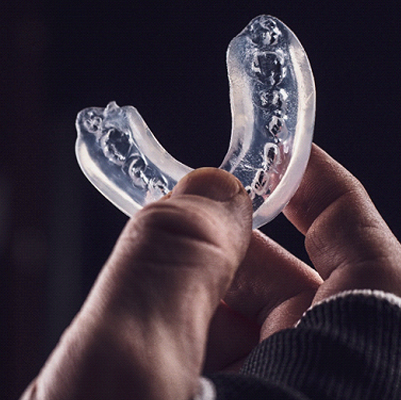 A person holding a clear mouthguard used to protect teeth while engaging in sports