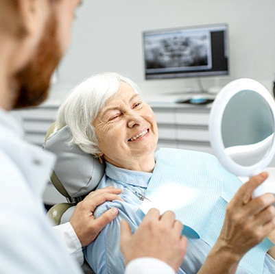Older woman in dental chair smiling.