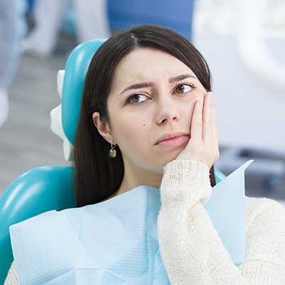 Woman at root canal appointment holding cheek