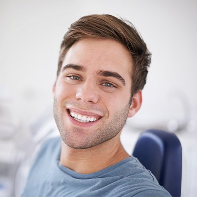 Young man in dental chair smiling after wisdom tooth extraction