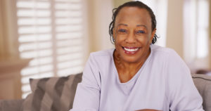 Smiling woman knowing how long do dental implants last