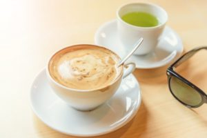 cup of green tea next to a cup of coffee