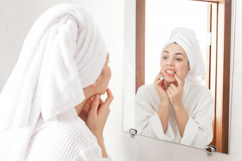 Woman examining her teeth in the bathroom mirror